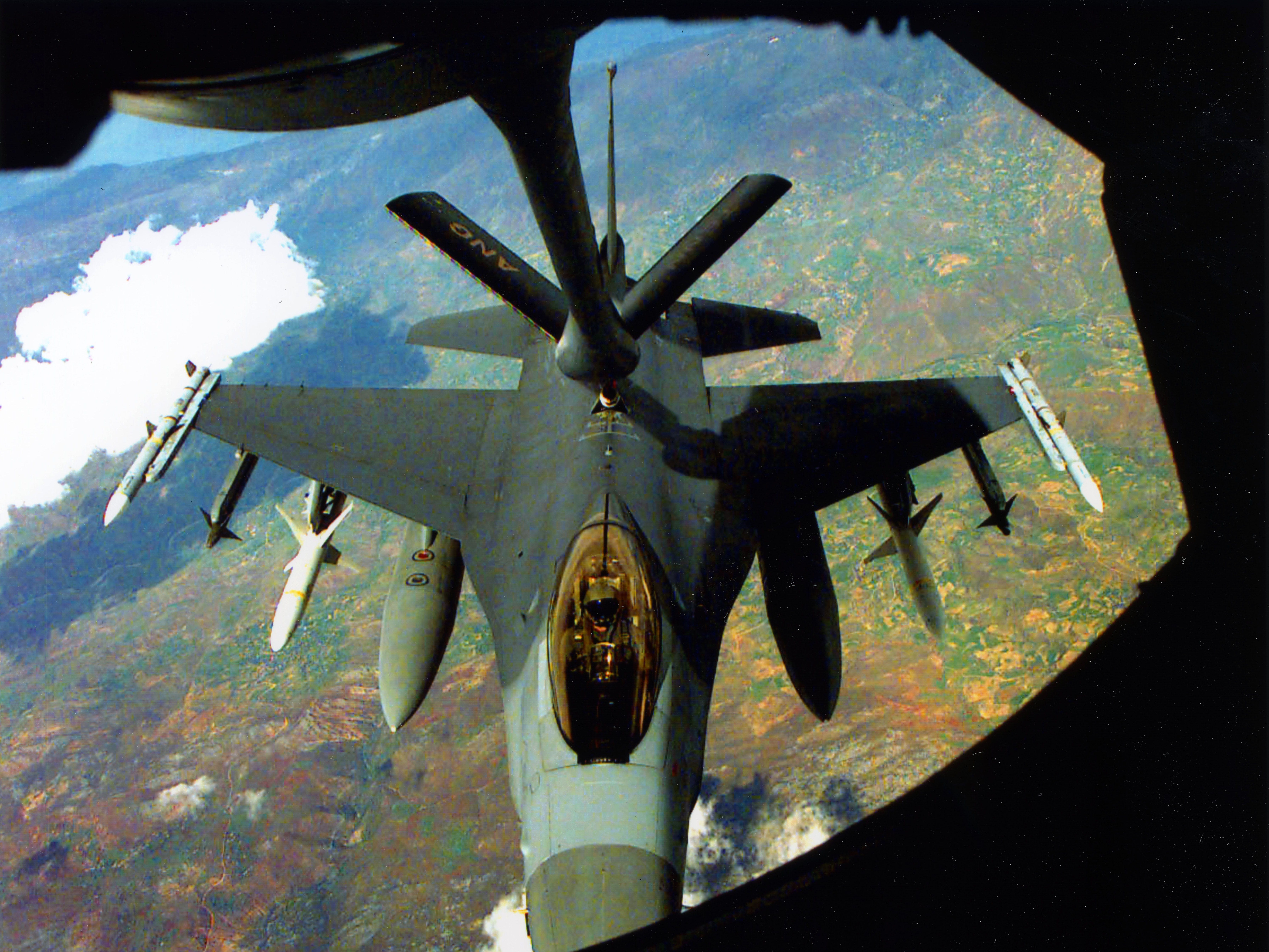 An Air Force F-16 fully loaded with missiles, gets a fuel refill, courtesy of a Tennessee Air National Guard 134th Air Refueling Wing tanker April 28, 1999. Under the fighter's wing are, from the outside, Sidewinder and Sparrow missiles, HARM anti-radar site missiles and fuel tanks.