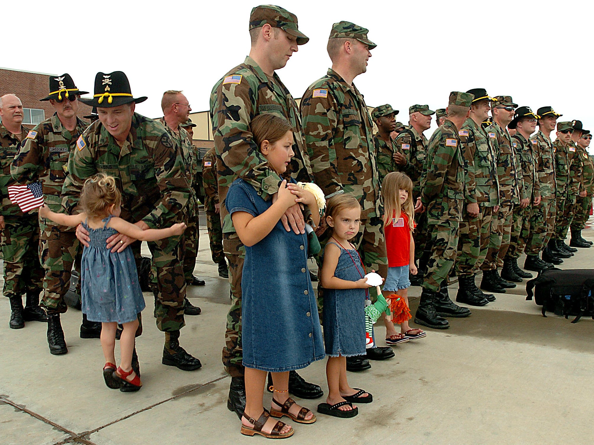 Sgt. Dale Long steps out of formation to pick up his daughter, Kiely, 3, just as the squadron was dismissed to go home with their families. In front of Long is Spc. Charles Van Valkenburgh with his two daughters Kakenzy, 7, and Mallory, 3. Members of the4th Squadron of the 278th return home to hugs and kisses on the tarmac at their hanger at McGhee Tyson Airbase Thursday afternoon.