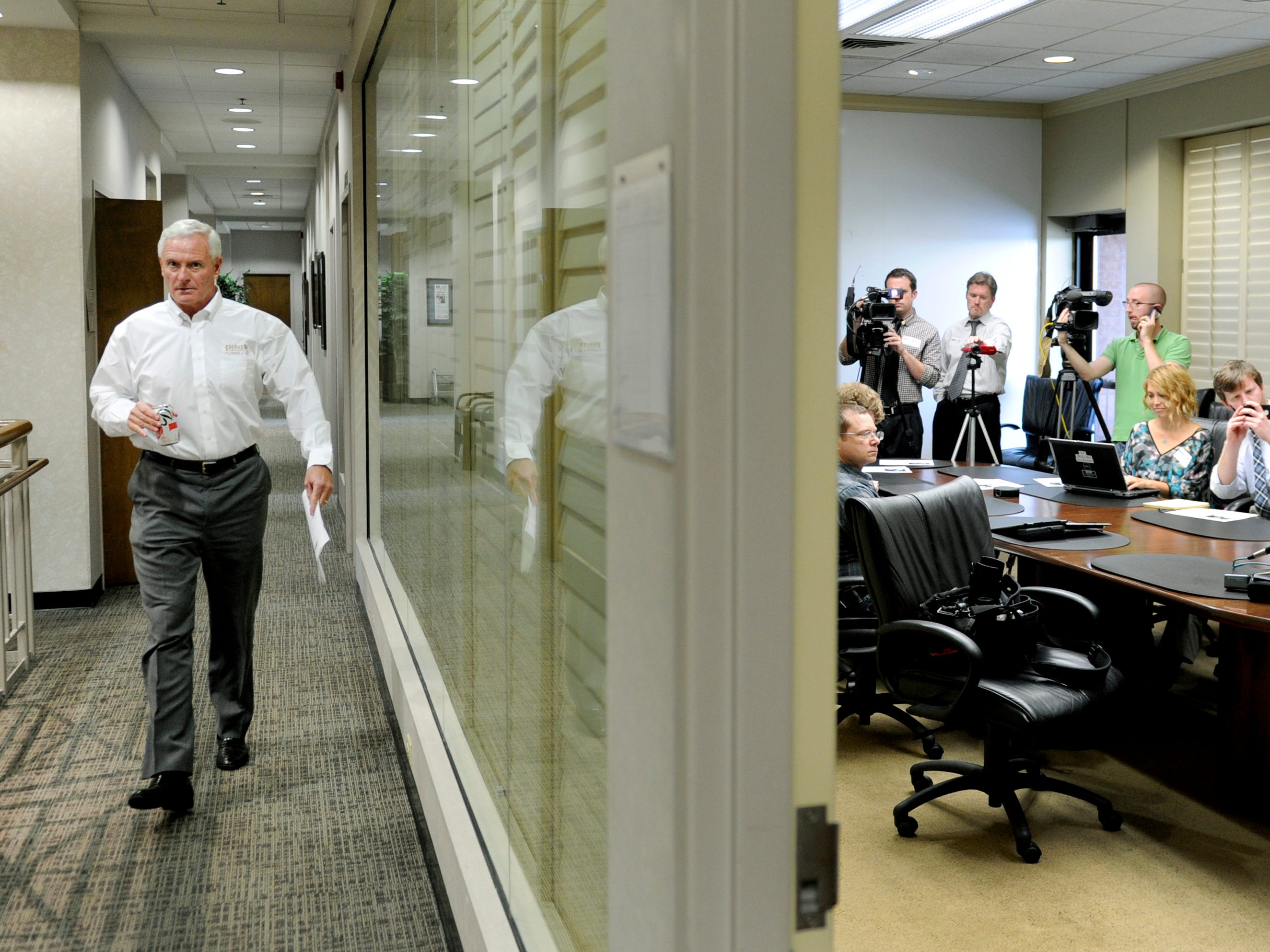 Pilot Flying J CEO Jimmy Haslam walks down the hall from his office to waiting members of the media in the boardroom at their Knoxville headquarters Monday, Apr. 22, 2013. To the left is Tom Ingram, founder of The Ingram Group, who is helping Pilot Flying J during this time.