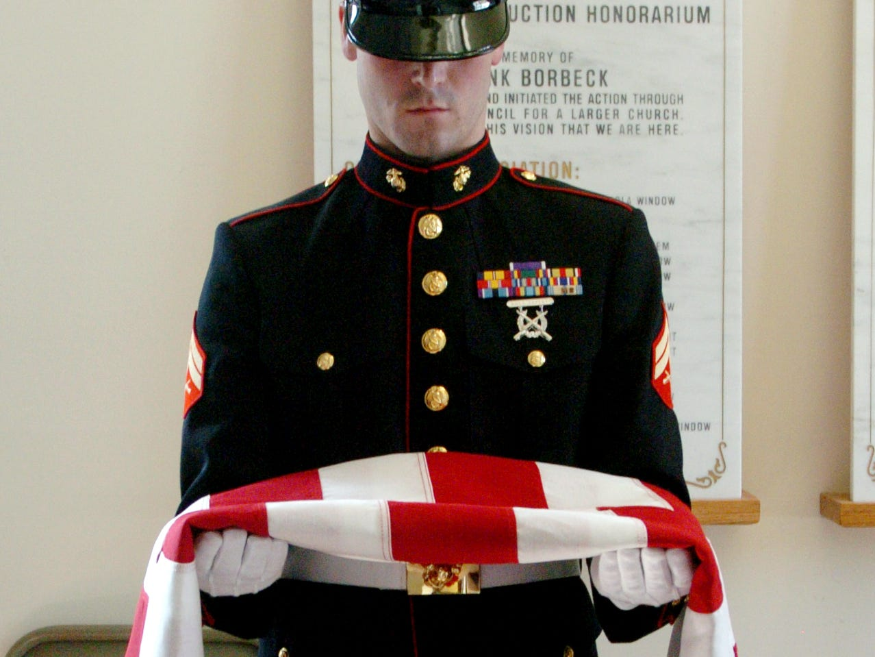A member of the Marine Honor Guard holds the flag from the casket of  Marine Sergeant Michael Harvey Ferschke, Jr. during the funeral service inside Our Lady of Fatima Catholic Church in Alcoa. During the service inside the church the casket was covered with the pall, which symbolizes the white garment received at baptism, and covers the casket during the celebration of the liturgy.
