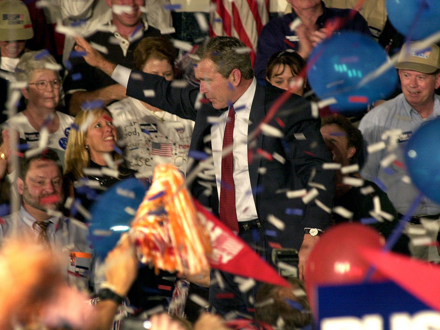 George W. Bush waves to supporters as confetti falls from the roof inside in the gym of South-Doyle Middle School Tuesday afternoon. Bush was surrounded by cheering banner waving supporters during the hour long rally. 10-24-2000