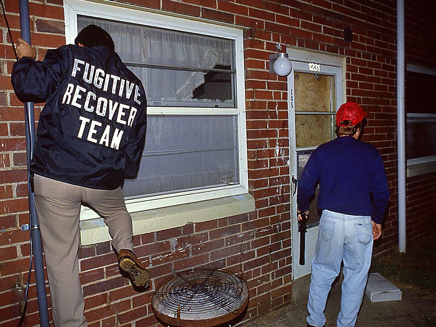 Lynn Davis, left, of A-1 Bonding Co. and Ray Phillips of Ace Bonding Co. peer into an apartment Oct. 5, 1991 hoping to find a man who they say skipped bail made by both companies. The man was not at the residence, but the bondsmen Sid they will keep searching.