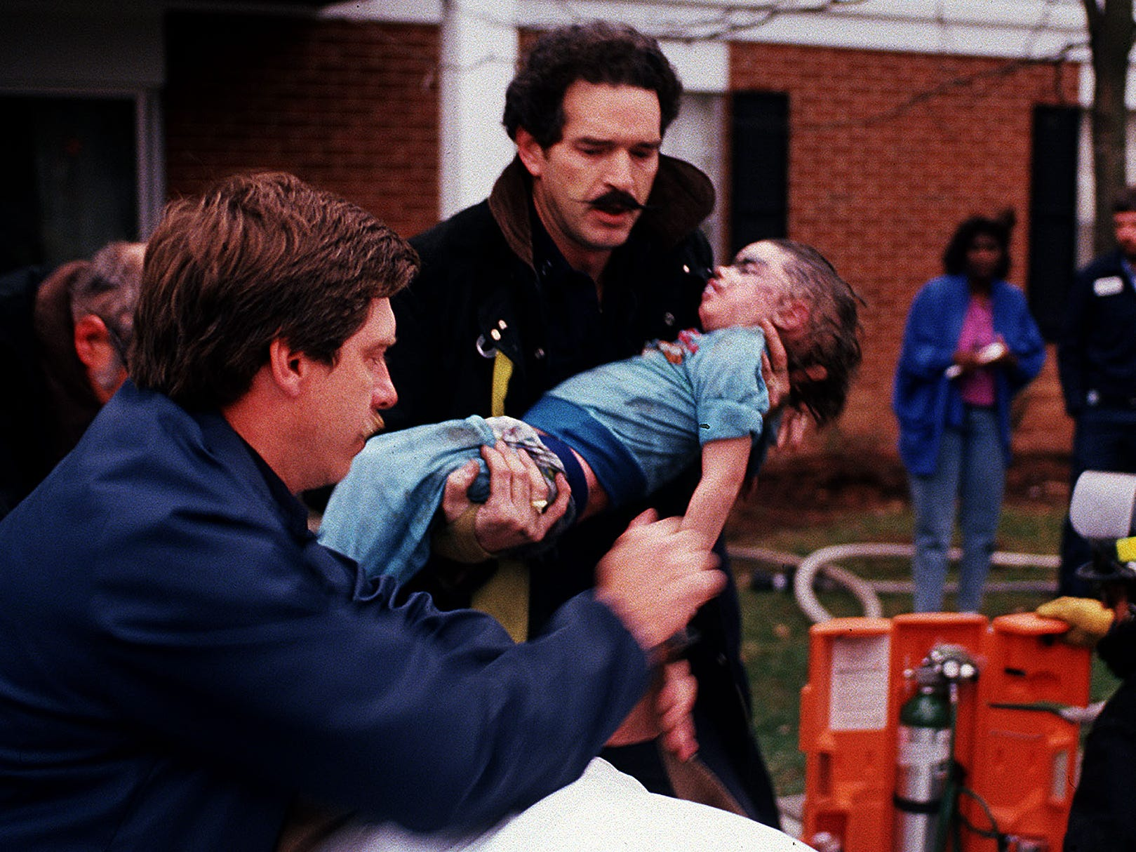Knoxville firefighter Roy Wilson carries Philip Colby Galloway to a waiting stretcher held by emergency medical technician Don Lee. The child was rescued from a burning apartment in New College Homes Dec 19, 1988.