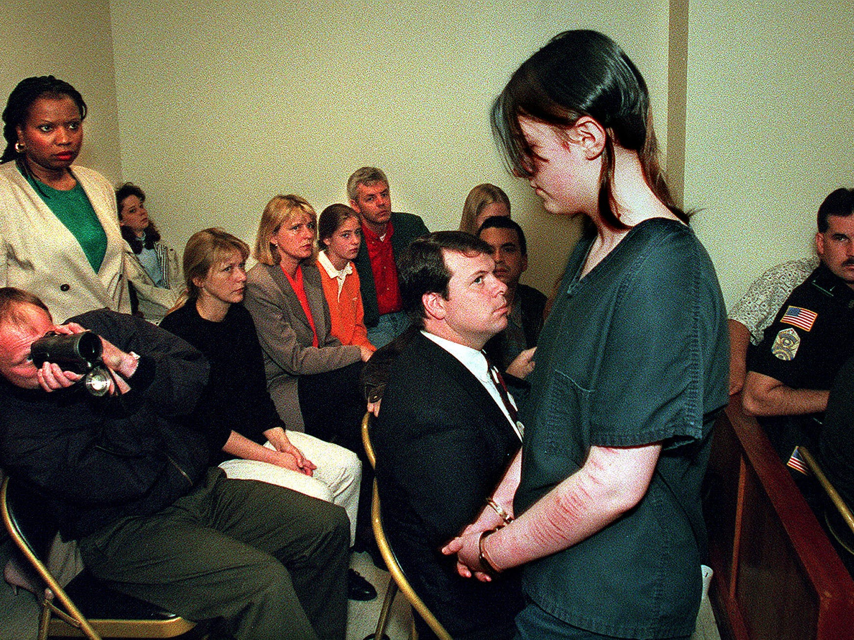 Eugen Lillelid photographs Natasha Walden Cornett as she leaves court April 15, 1997 after her arraignment in the slaying of Lillelid's brother, sister-in-law and their daughter. Relatives seated next to Eugen are, from left, Randi Heier, Marit Ekron and Linda and Odd Heir. Ed Runyonm seated in front of Eugen, and Brenda Hunter, standing behind, are members of the victim's church.