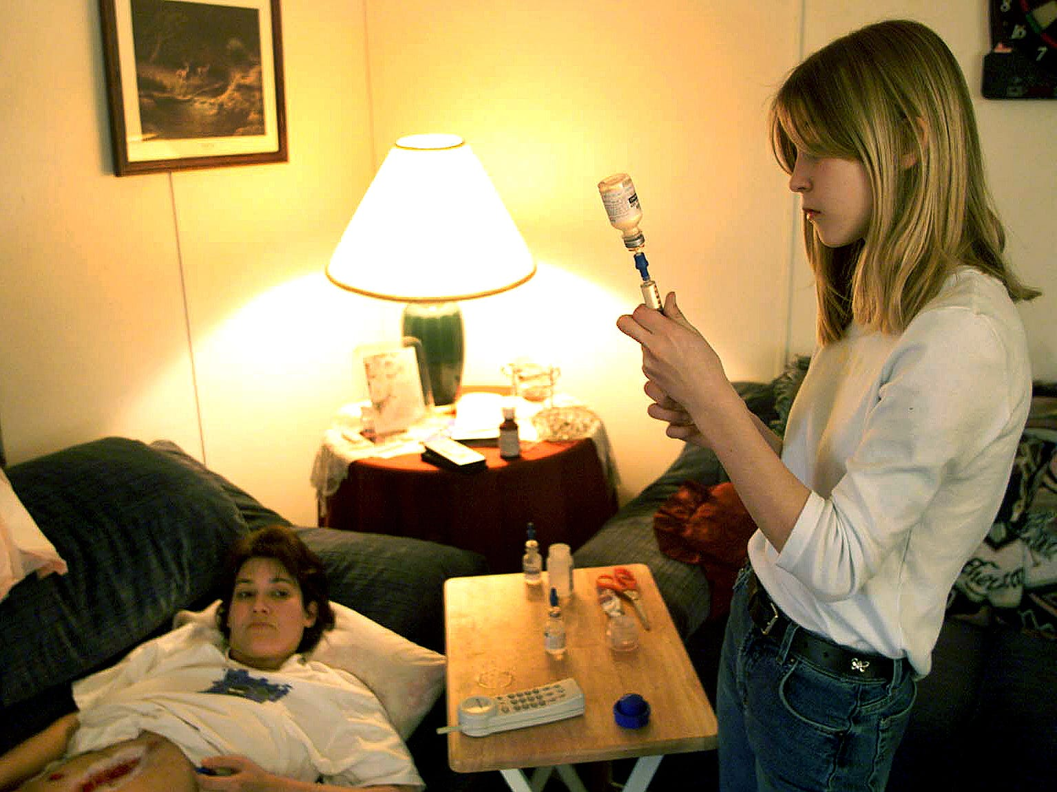 A car accident left Tammie Harless in need of help from TennCare. Her oldest daughter, Britani Gamer, 12, prepares a needle of sodium chloride in the living room of their Union County home to slush out her mother's feeding tube. The flushing is a twice-daily ritual. March 19, 2000
