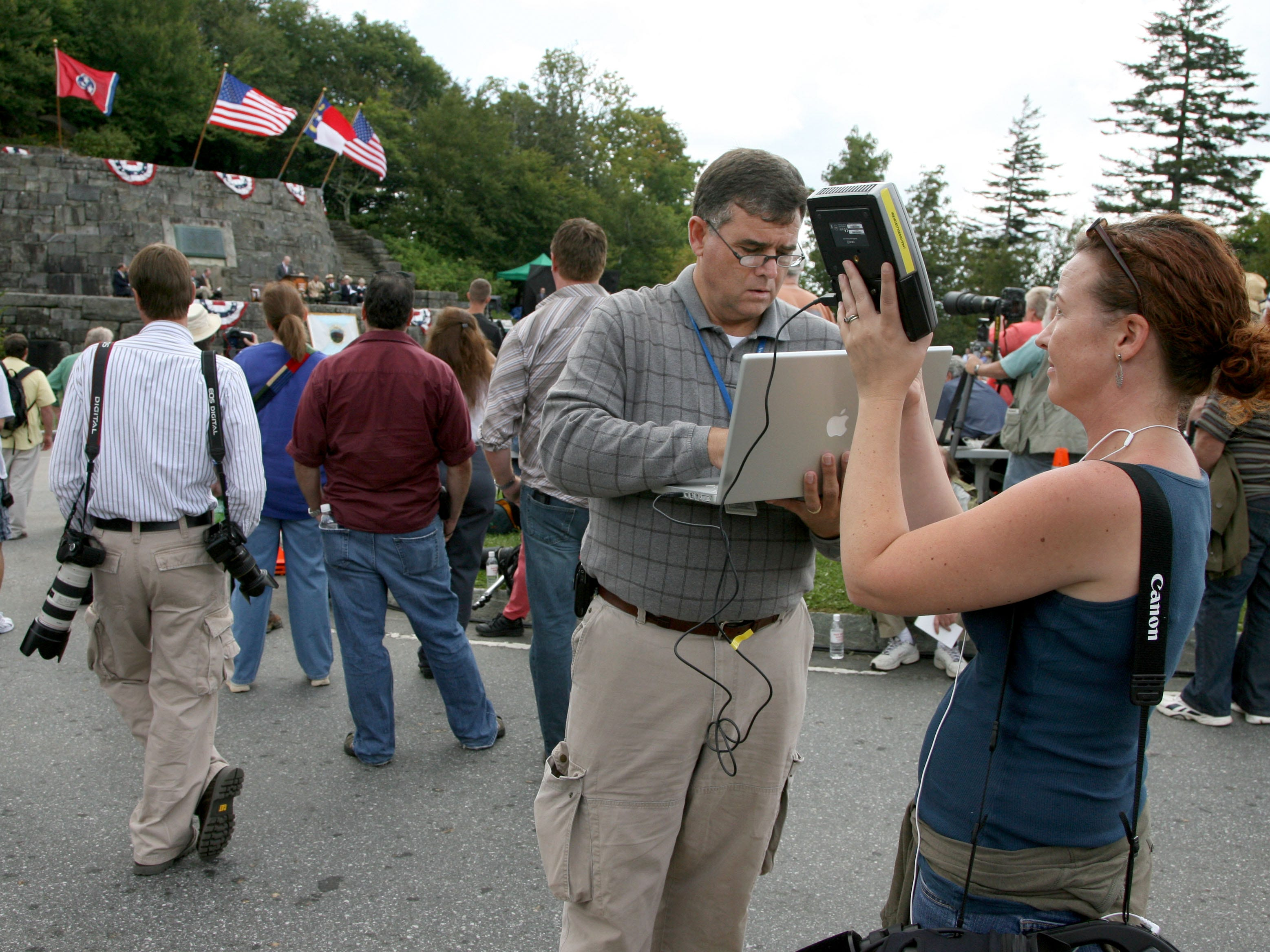 Knoxville News Sentinel staff photographer Michael Patrick, center, attempts to use a satellite phone to transmit photos as videographer Erin Chapin, right, helps during the 75th anniversary re-dedication of the Great Smoky Mountains National Park on Wednesday, September 2, 2009 at Newfound Gap.