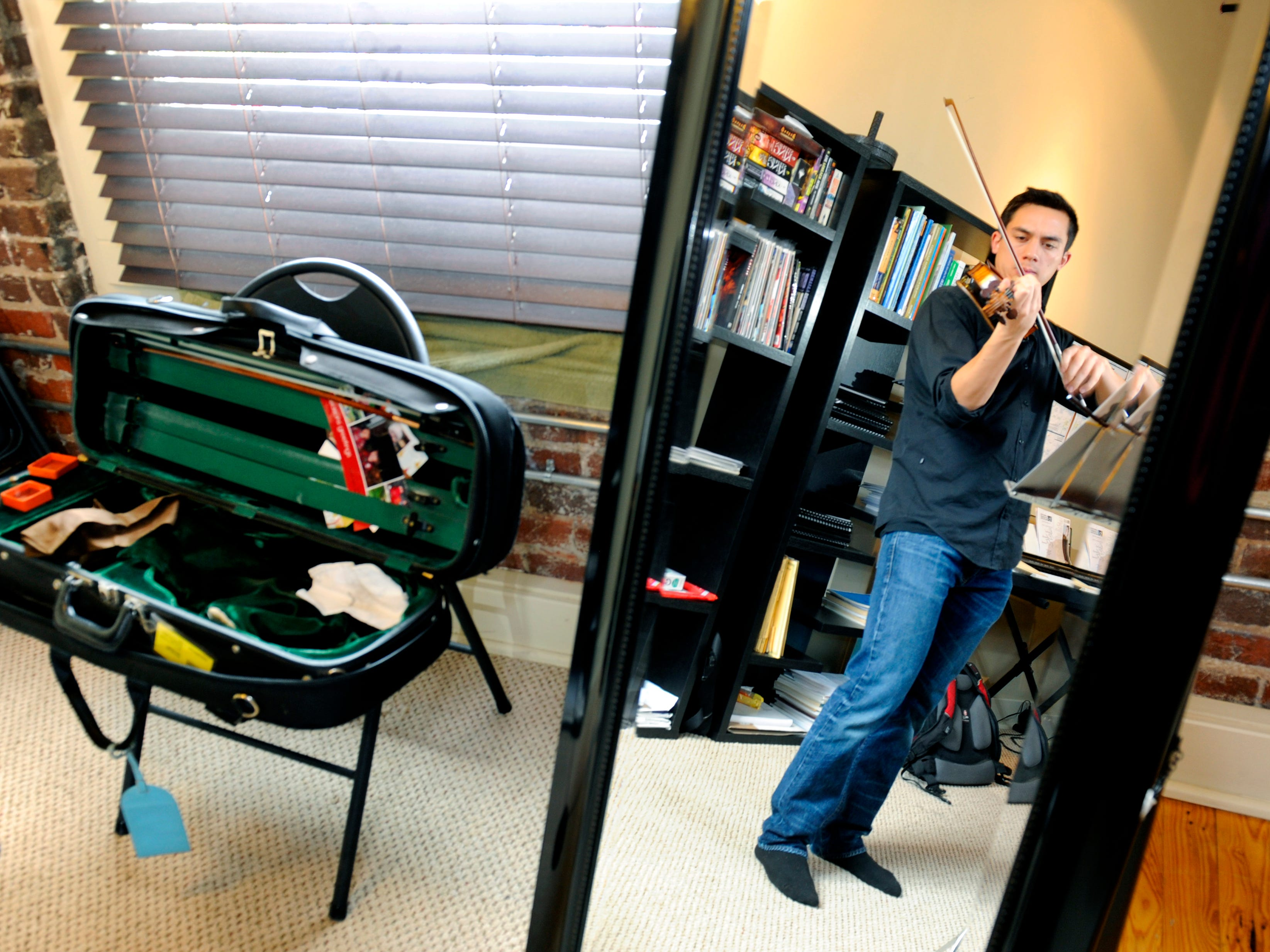 Portraits of people showing their personality is often a difficult assignment. KSC Concertmaster Gabriel Lefkowitz was practicing in his home on Jackson Ave in Knoxville. I used a mirror he uses to check his posture while he is practicing to make a photo of his rehearsal.