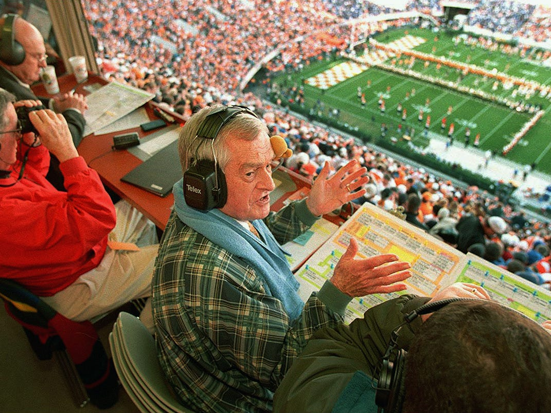 """John Ward talks to staff in the broadcast booth as the Tennessee football team runs through the """"T"""". To the far left is Bill Anderson, Russ Bebb (red coat), John Ward (center) and spotter Randy O'Neal. 1998."""