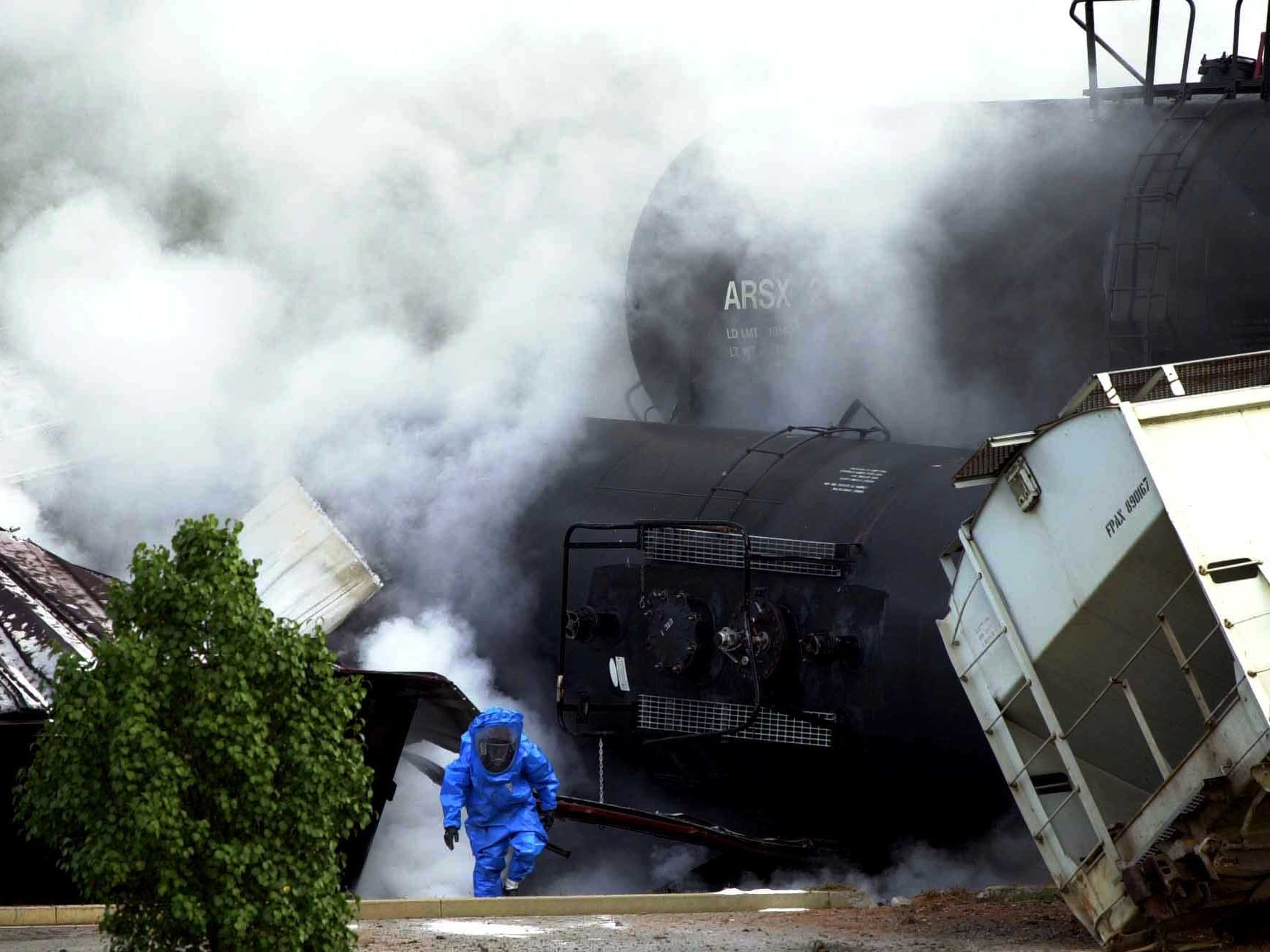 A hazmat worker climbs up from the wreckage of several railroad cars carrying thousands of gallons of sulfuric acid after they derailed, ruptured and sent plumes of corrosive gas into the air Sunday morning.  The crash is at Anchor Park off Turkey Creek Rd in Farragut.