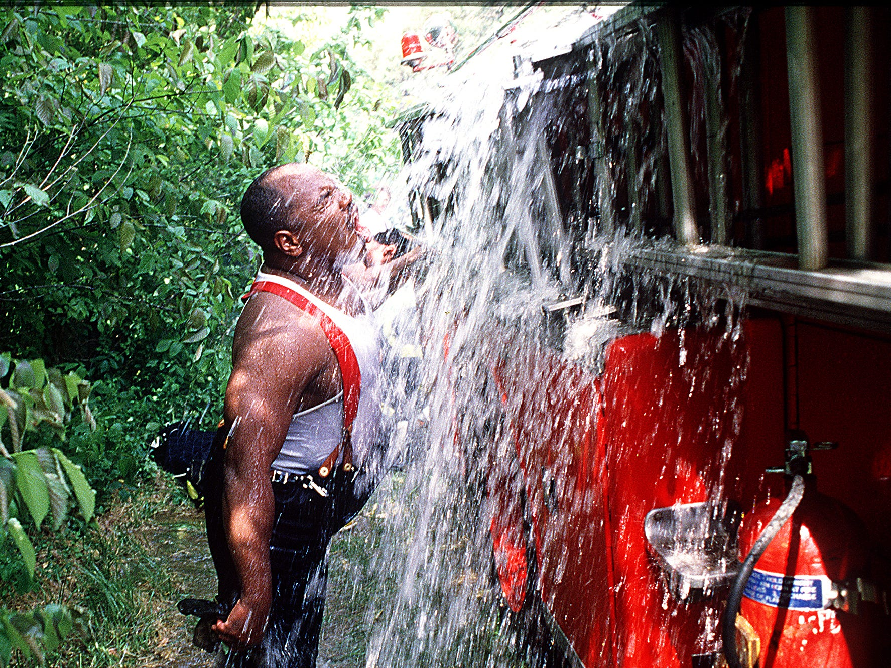 Knoxville firefighter James Anderson takes advantage of the overflow from a truck Thursday, May 16, 1990 to cool down after battling the old Halls Elementary school blaze.