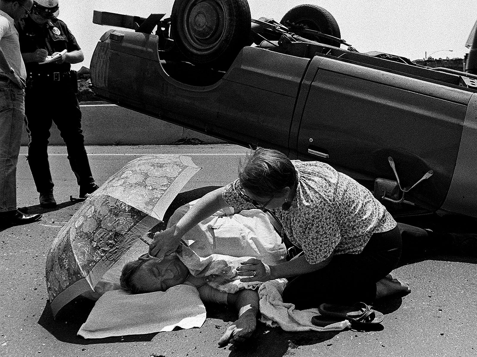 James Payne, 55, gets a helping hand from a passing motorist after his truck overturned on I-40 east near Seventeenth Street. Payne was treated at Baptist after the 12:25 p.m. accident July 2, 1980. Nell Jones traveling from N.C. to Texas stopped and placed the umbrella over Payne and a pillow under his head until an ambulance arrived.