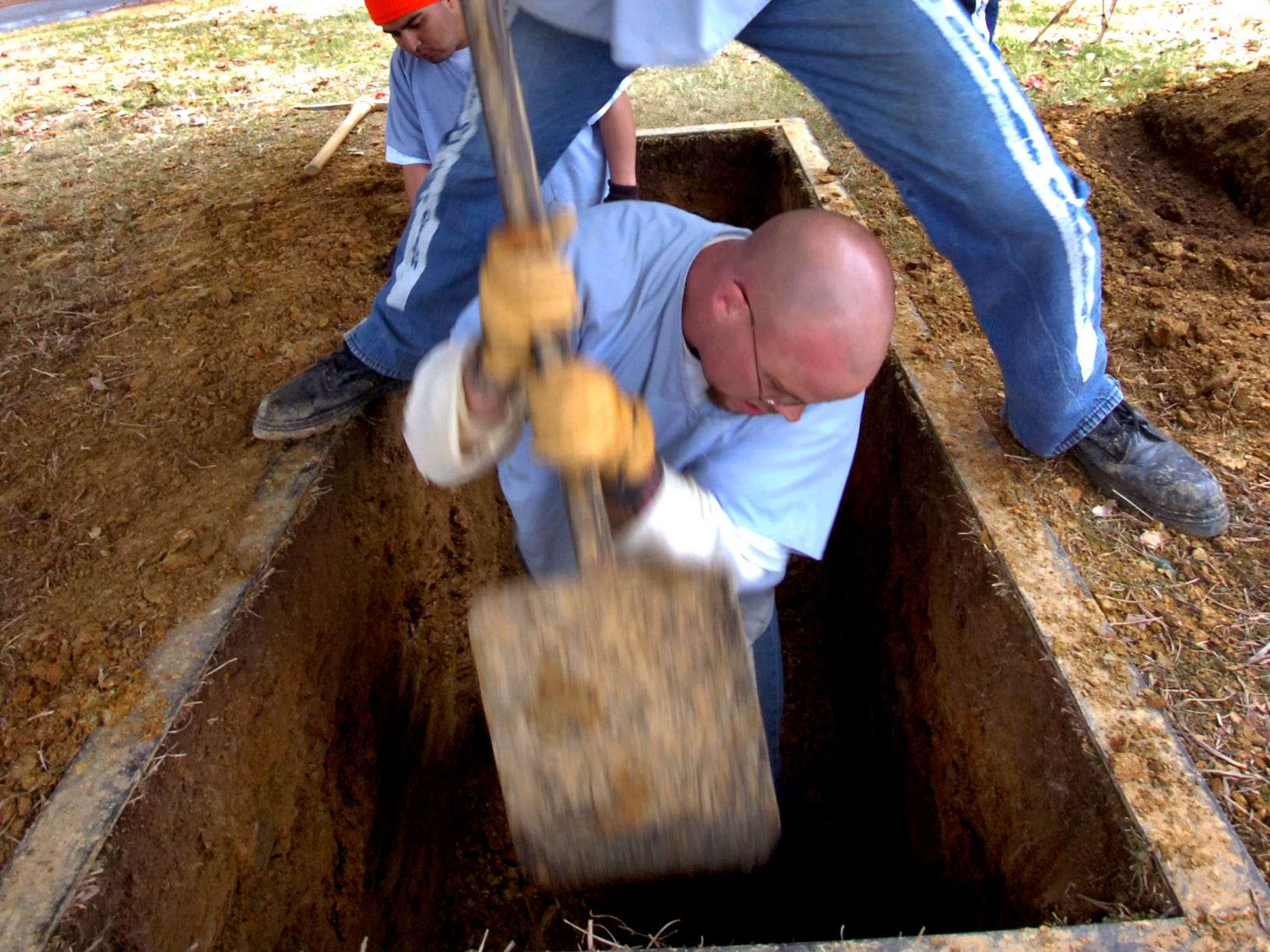 Prisoners from Morgan County Regional Correctional Complex regularly hand dig graves for residents of Morgan and Roane Counties who have financial need. Inmates Brent Hutcheson, top, and Mitch Stout use a 60-pound edger to smooth the sides of the grave the team was digging in Roane County Feb, 21, 2008. The inmates are pre-selected as safe to work outside the prison property enjoy not only getting outside but helping the community.