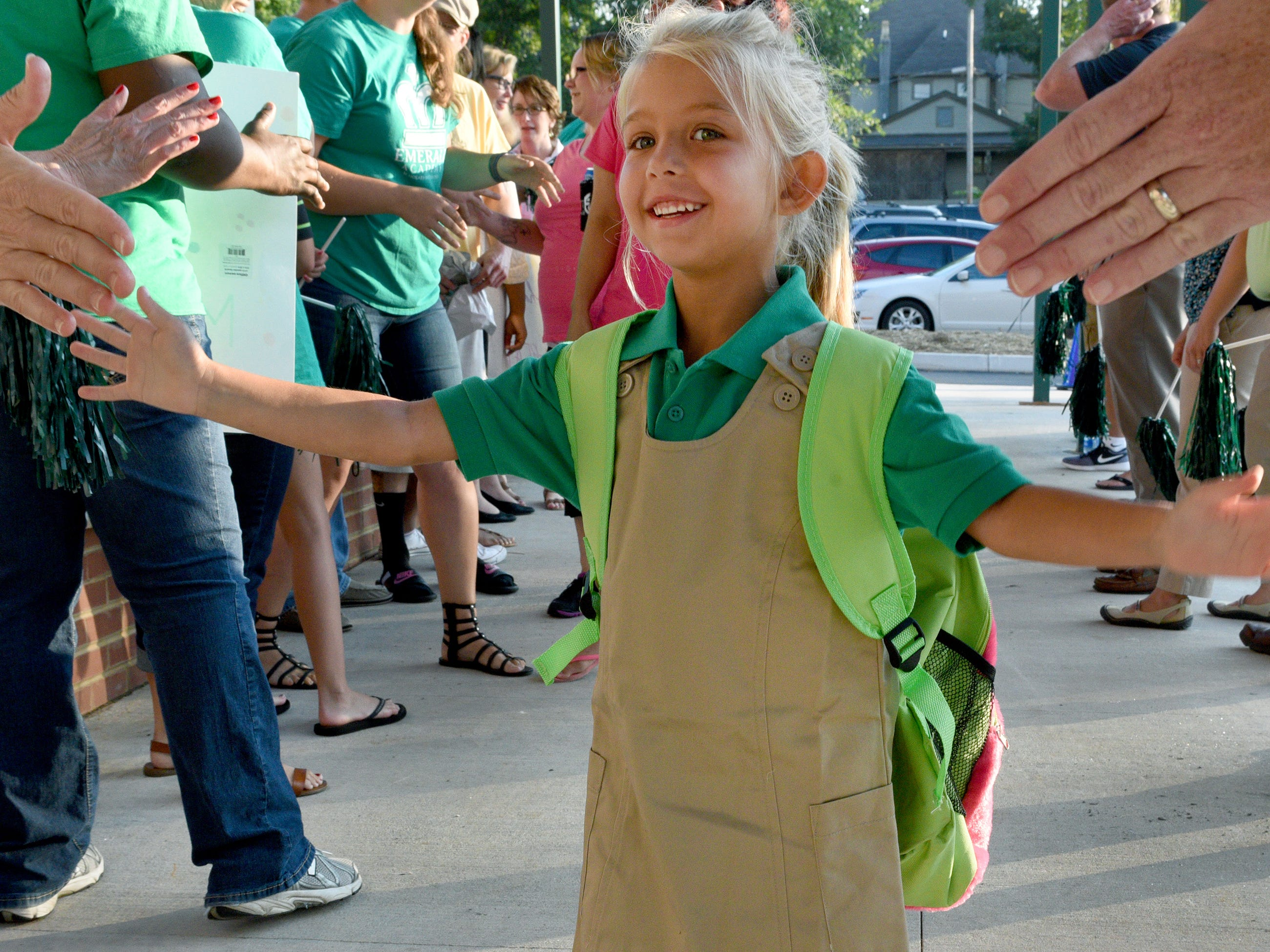 Maddison Clarkson, 6, walks the gauntlet of teachers and staff as she arrives for the first day of classes at Emerald Academy, Knoxville's first charter school Monday, Jul. 27, 2015. Emerald Academy is housed in the former Moses Center on Carrick Ave in Lonsdale.