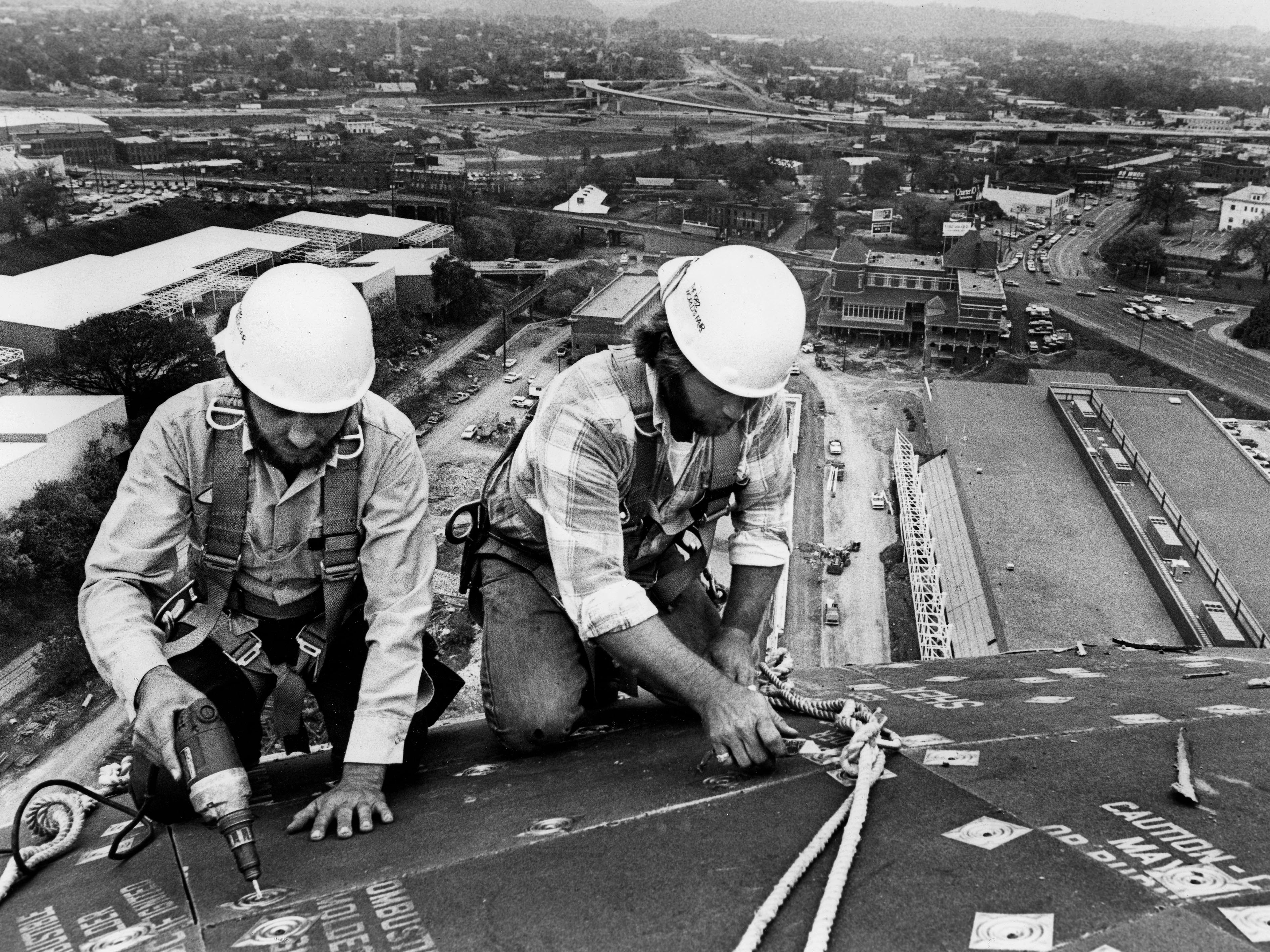 J.E. Gibson, left, and Donnie Cusick, right, both from Seymour, work on installing sheet metal far above ground on the top of the Sunsphere on October 23, 1981.