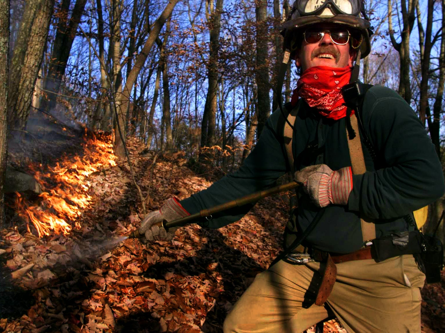 Marlow fire Dept. Ast. Chief Win Matheny talks to his partner as he sprays water on the fire line on the hill about 200-yards behind Tamya West's home on Dutch Valley Rd just outside Oliver Springs. West and her father, Johnny Wilson said the fire has burned on and off for two weeks on the ridge behind them. 11/16/1999.