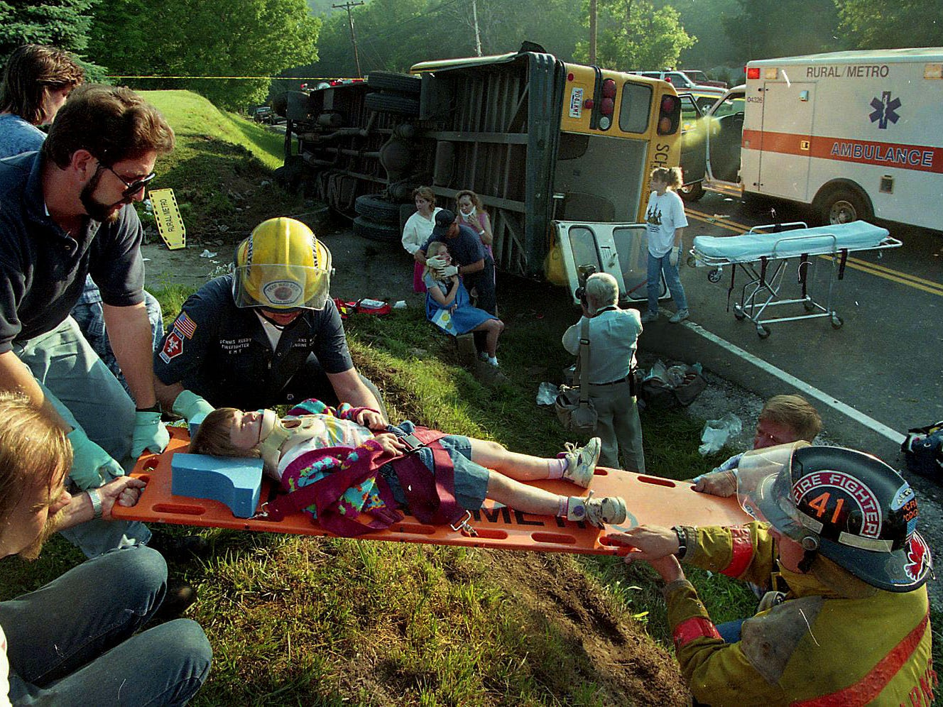 Rural/Metro emergency workers take one of the 25 injured students to a waiting ambulance after their bus overturned on Lovell Rd Tuesday, May 21, 1996.
