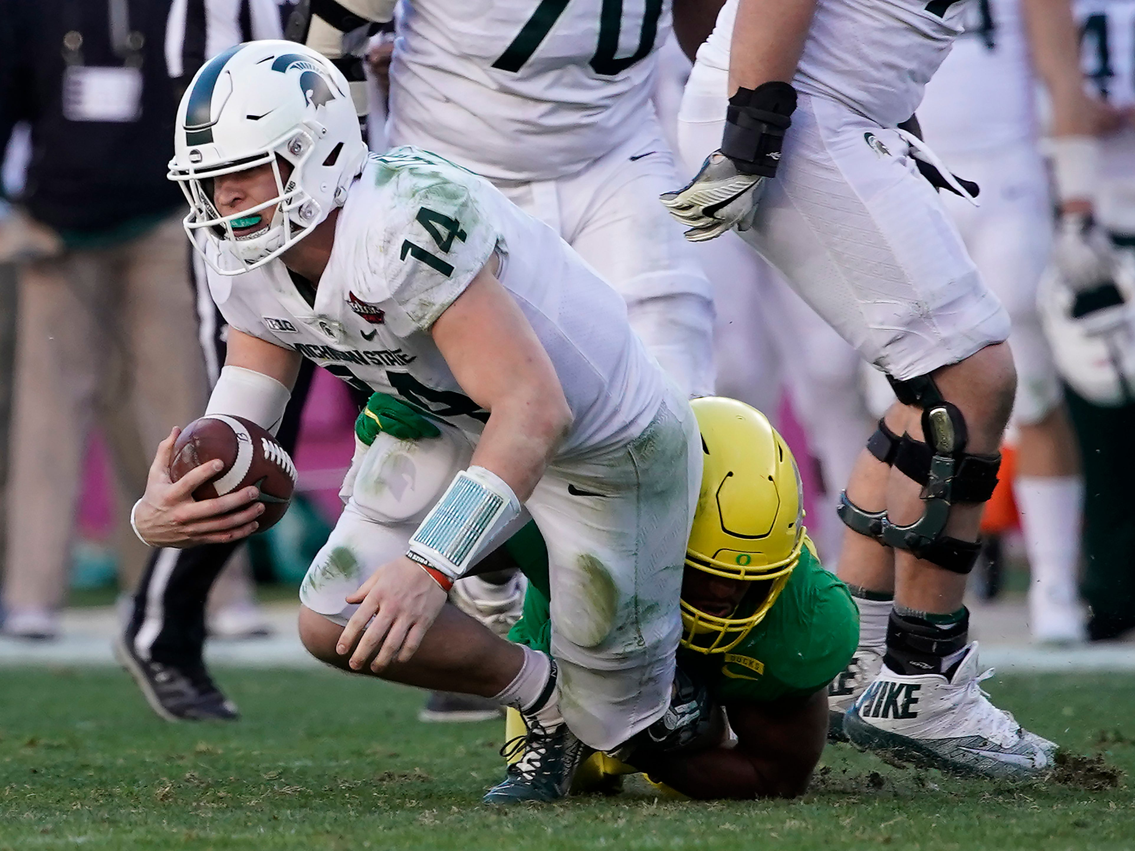Michigan State quarterback Brian Lewerke (14) is sacked by Oregon linebacker Justin Hollins (11) during the second half of the Redbox Bowl NCAA college football game Monday, Dec. 31, 2018, in Santa Clara, Calif.
