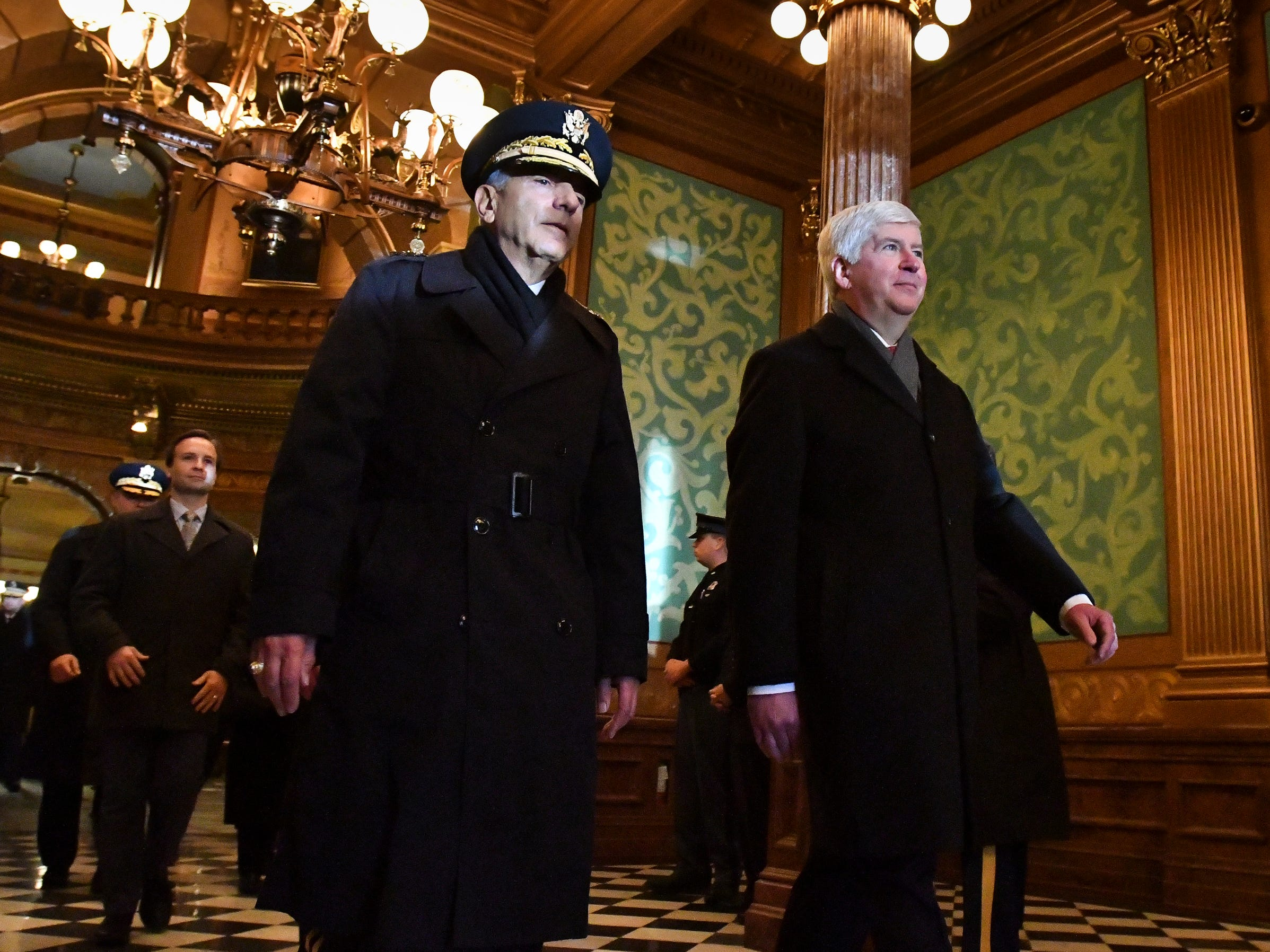 Former Michigan Governor Rick Snyder is escorted by a member of the military to the Capitol steps for the 2019 inauguration Tuesday, Jan. 1, 2019.