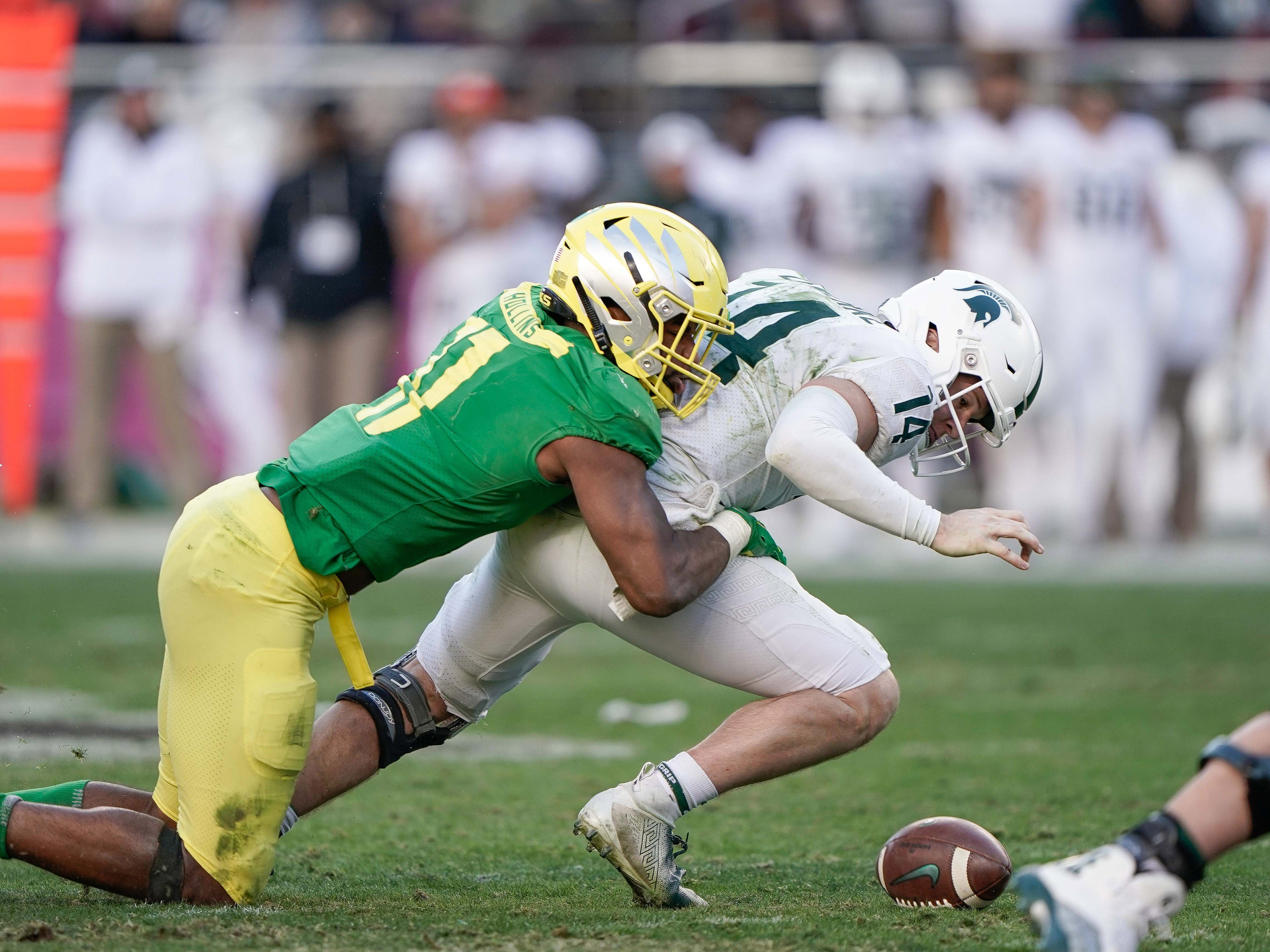 Oregon Ducks linebacker Justin Hollins (11) forces a fumble by Michigan State Spartans quarterback Brian Lewerke (14) during the fourth quarter at Levi's Stadium.