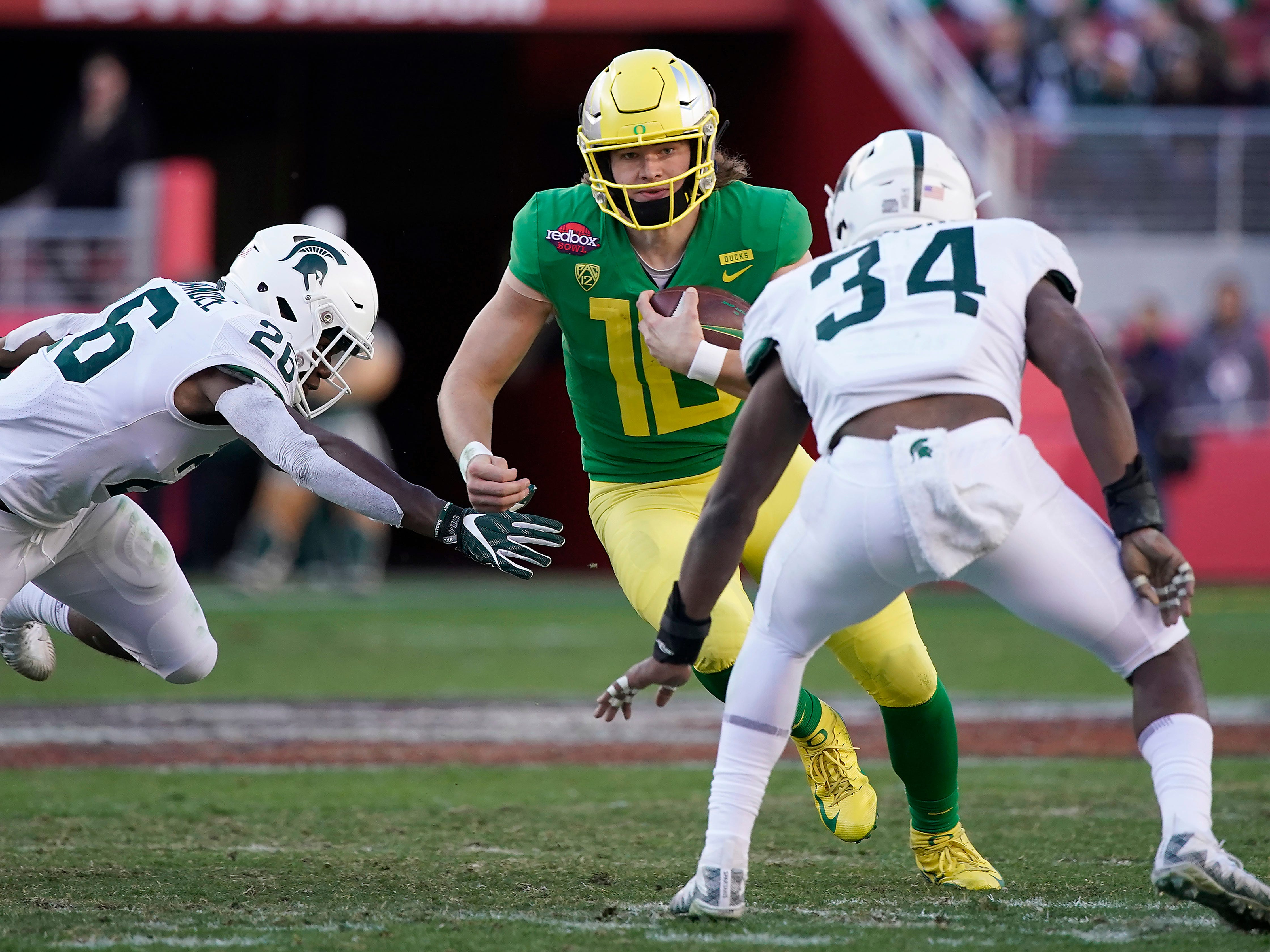 Oregon quarterback Justin Herbert (10) scrabbles out of the pocket between Michigan State linebackers Brandon Bouyer-Randle (26) and Antjuan Simmons (34) during the second half of the Redbox Bowl NCAA college football game Monday, Dec. 31, 2018, in Santa Clara, Calif. Oregon won 7-6.