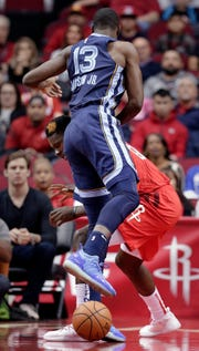 Memphis Grizzlies forward Jaren Jackson Jr. (13) lands on top of Houston Rockets center Clint Capela as he tries to pick up the ball during the first half of an NBA basketball game Monday, Dec. 31, 2018, in Houston. (AP Photo/Michael Wyke)