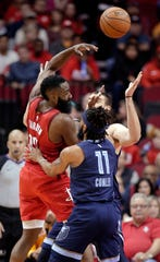 Houston Rockets guard James Harden (13) passes the ball over Memphis Grizzlies guard Mike Conley (11) and center Marc Gasol, back, during the first half of an NBA basketball game Monday, Dec. 31, 2018, in Houston. (AP Photo/Michael Wyke)