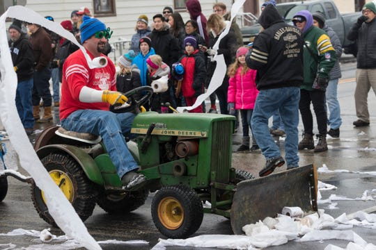 A man scrapes up toilet paper tossed during the Toilet Bowl Parade.