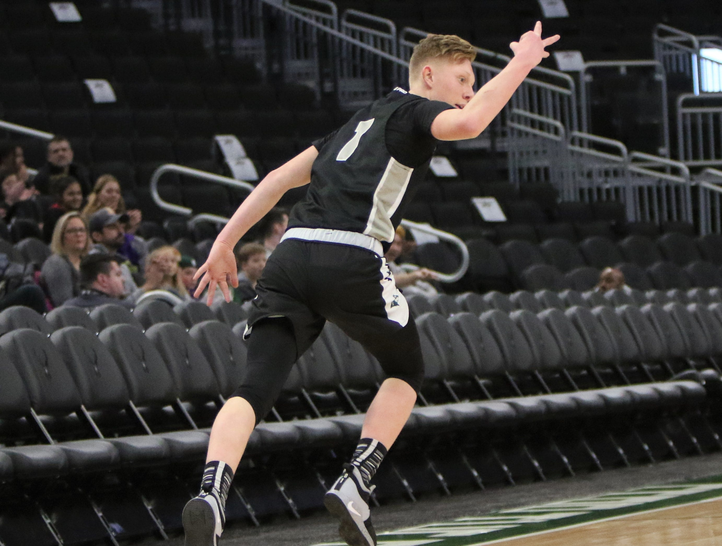 West Allis Hale guard Matt Behling hoists up three fingers after sinking a three-pointer against New Berlin Eisenhower on Tuesday, Jan. 1, at Fiserv Forum.