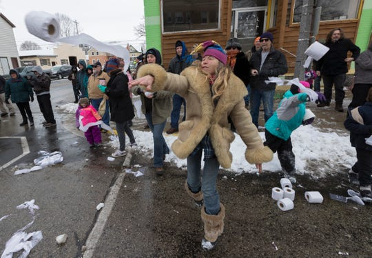 Kim Prescher launches a roll of toilet paper at a parade participant during the annual Toilet Bowl Parade.