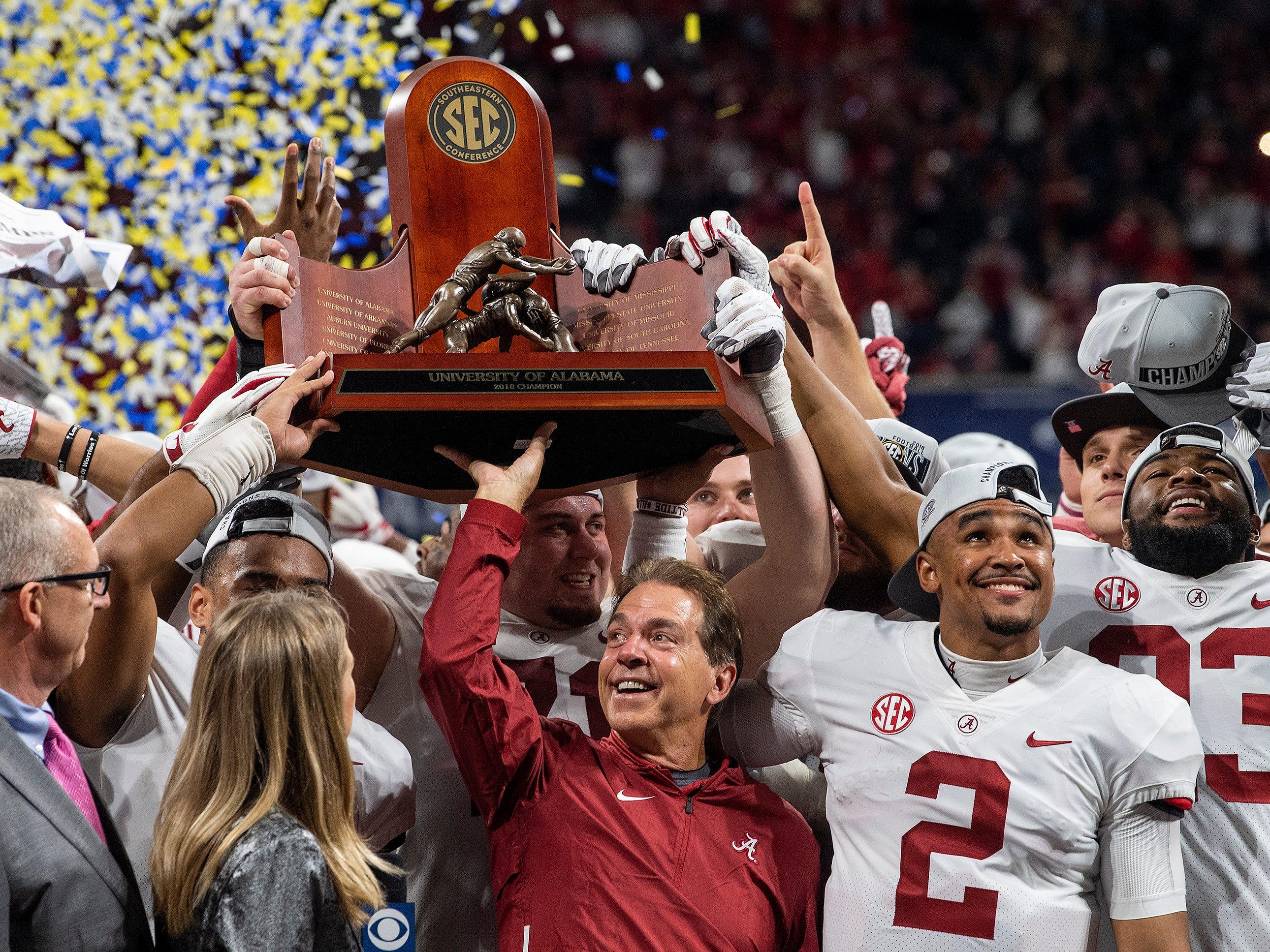Alabama head coach Nick Saban and Alabama quarterback Jalen Hurts (2) lift the SEC Trophy after defeating Georgia  in the SEC Championship Game at Mercedes-Benz Stadium in Atlanta on Saturday, Dec. 1, 2018.