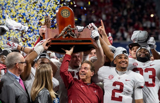 Alabama head coach Nick Saban and Alabama quarterback Jalen Hurts (2) lift the SEC Trophy after defeating Georgia  in the SEC Championship Game at Mercedes-Benz Stadium in Atlanta on Saturday, Dec. 1, 2018.