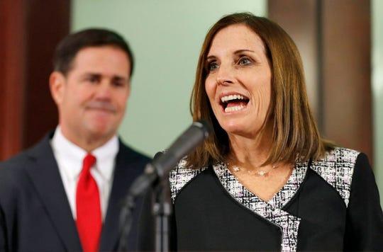 Rep. Martha McSally (R-Ariz.) speaks during a news conference in Phoenix as Arizona Gov. Doug Ducey (R) looks on.