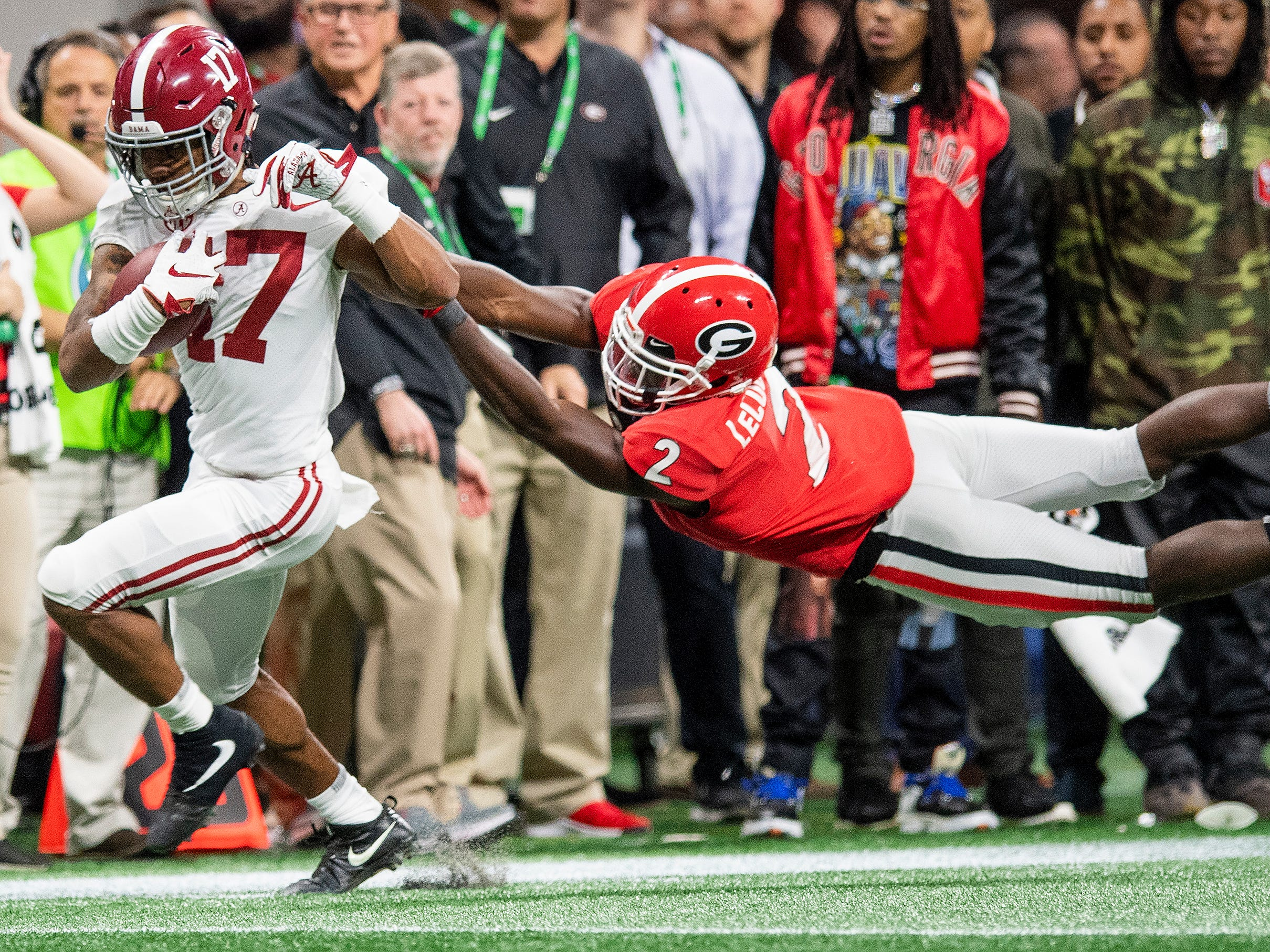Alabama wide receiver Jaylen Waddle (17) breaks the tackle of Georgia defensive back Richard LeCounte (2) on a long touchdown play in the SEC Championship Game at Mercedes Benz Stadium in Atlanta, Ga., on Saturday December 1, 2018.
