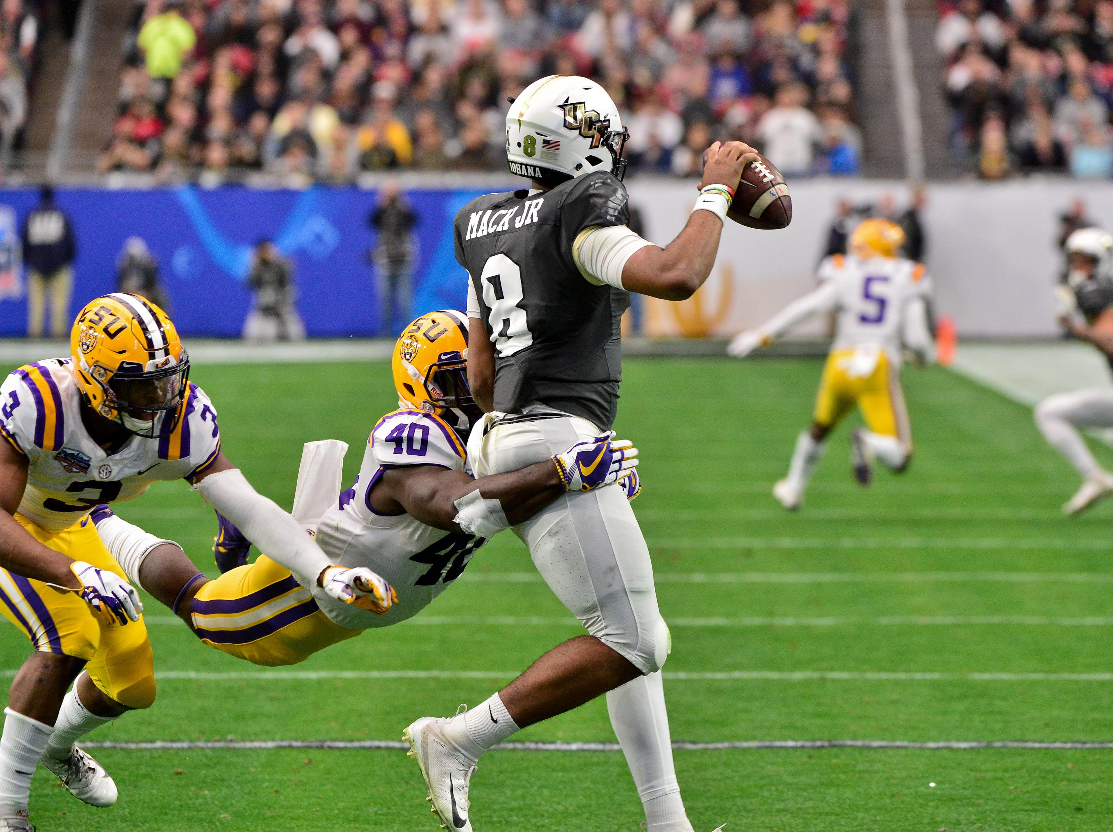 LSU Tigers linebacker Devin White (40) tackles UCF Knights quarterback Darriel Mack Jr. (8) during the first half in  the 2019 Fiesta Bowl at State Farm Stadium.