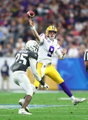 LSU Tigers quarterback Joe Burrow (9) throws a pass as he is hit by UCF Knights defensive back Kyle Gibson (25) in the second quarter of the 2019 Fiesta Bowl at State Farm Stadium.