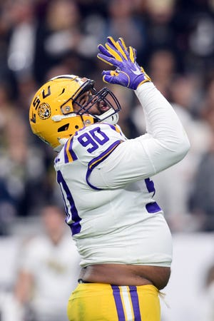 LSU Tigers defensive end Rashard Lawrence (90) celebrates a sack against the UCF Knights during the first half of the 2019 Fiesta Bowl at State Farm Stadium.