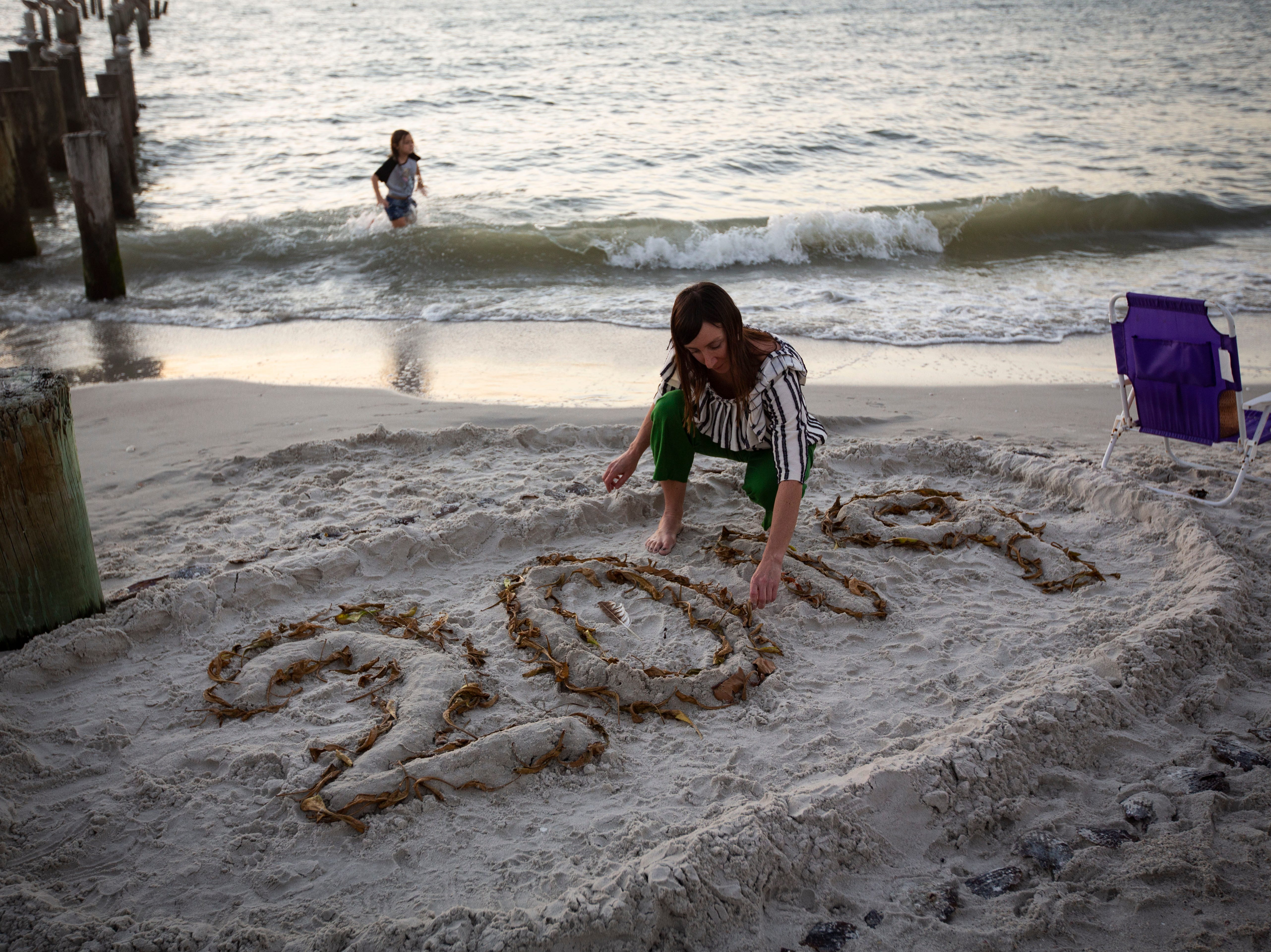 "Ann Schellinger decorates a hand-made new year's sign with seaweed, shells, and stones on Monday, Dec. 31, 2018, at the Naples Pier beach before the start of the annual fireworks. ""This is a Schellinger family tradition,"" Ann said. This tradition was initiated nearly three years back when they saw someone else make a similar sign in the sand."