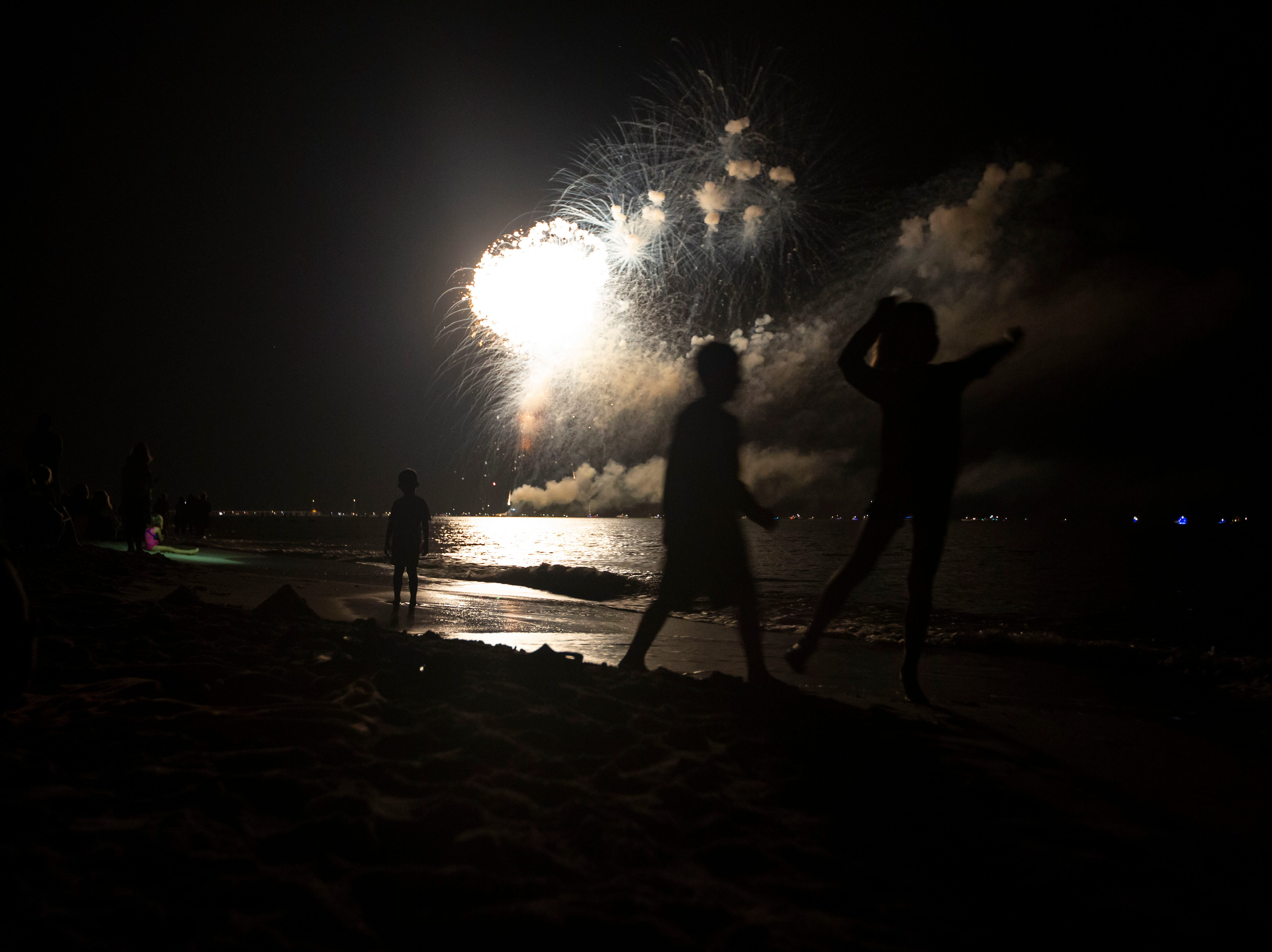 Children dance around by the Naples Pier beach as the the City of Naples concludes their New Year's Eve firework display on Monday, Dec. 31, 2018.