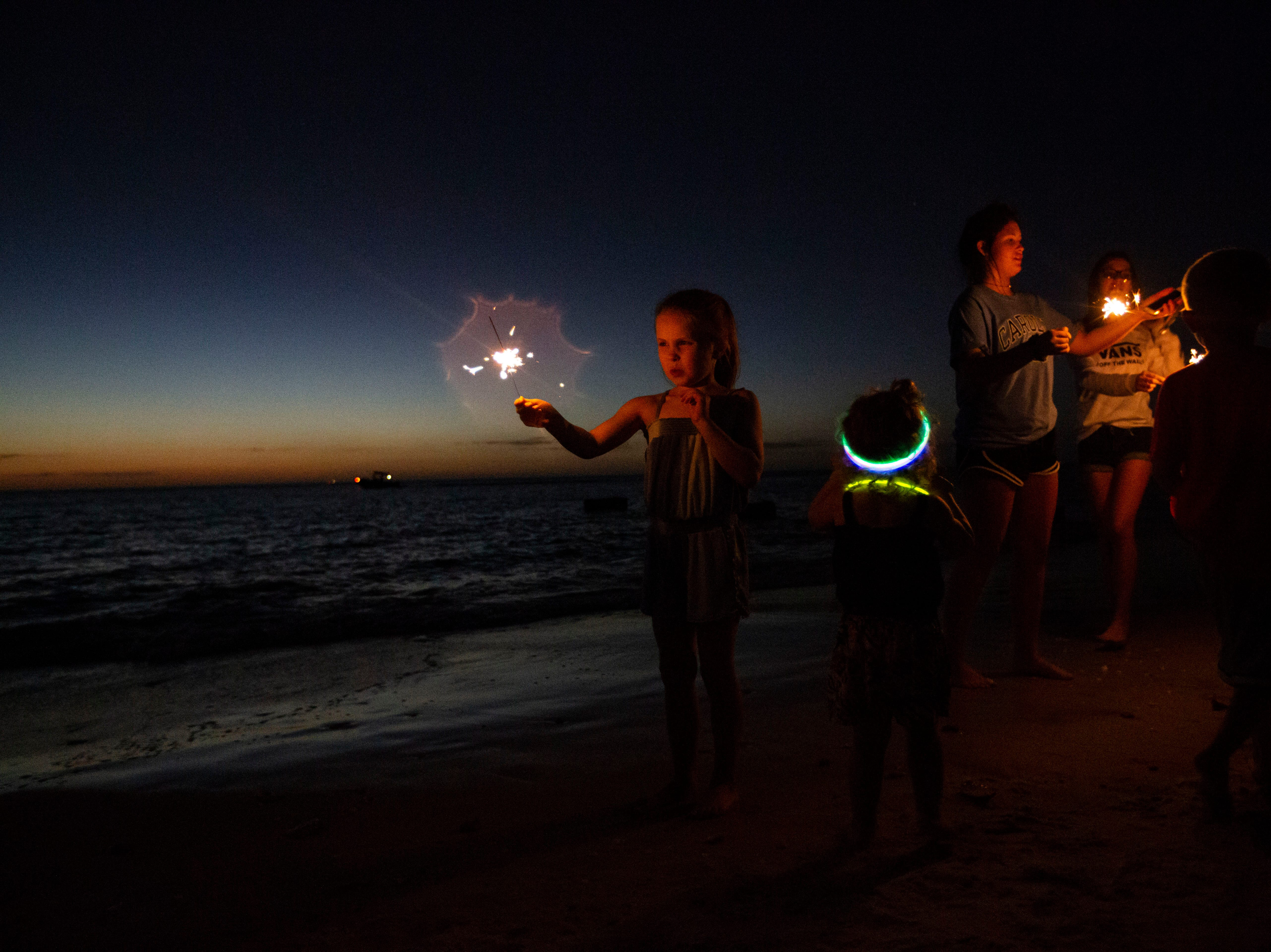 Marci Page, 6, reacts to her sparkler burning out on Monday, Dec. 31, 2018, at the Naples Pier beach, moments before the start of the annual New Year's Eve fireworks.