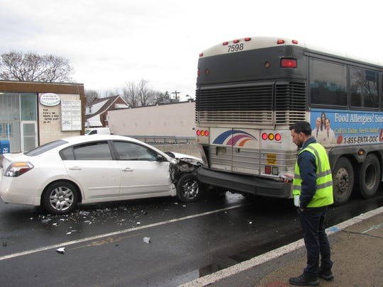 Car on Broadway in Fair Lawn after it struck bus Tuesday morning as bystander looks on. Police said they caught driver after fleeing scene and charged with DUI.