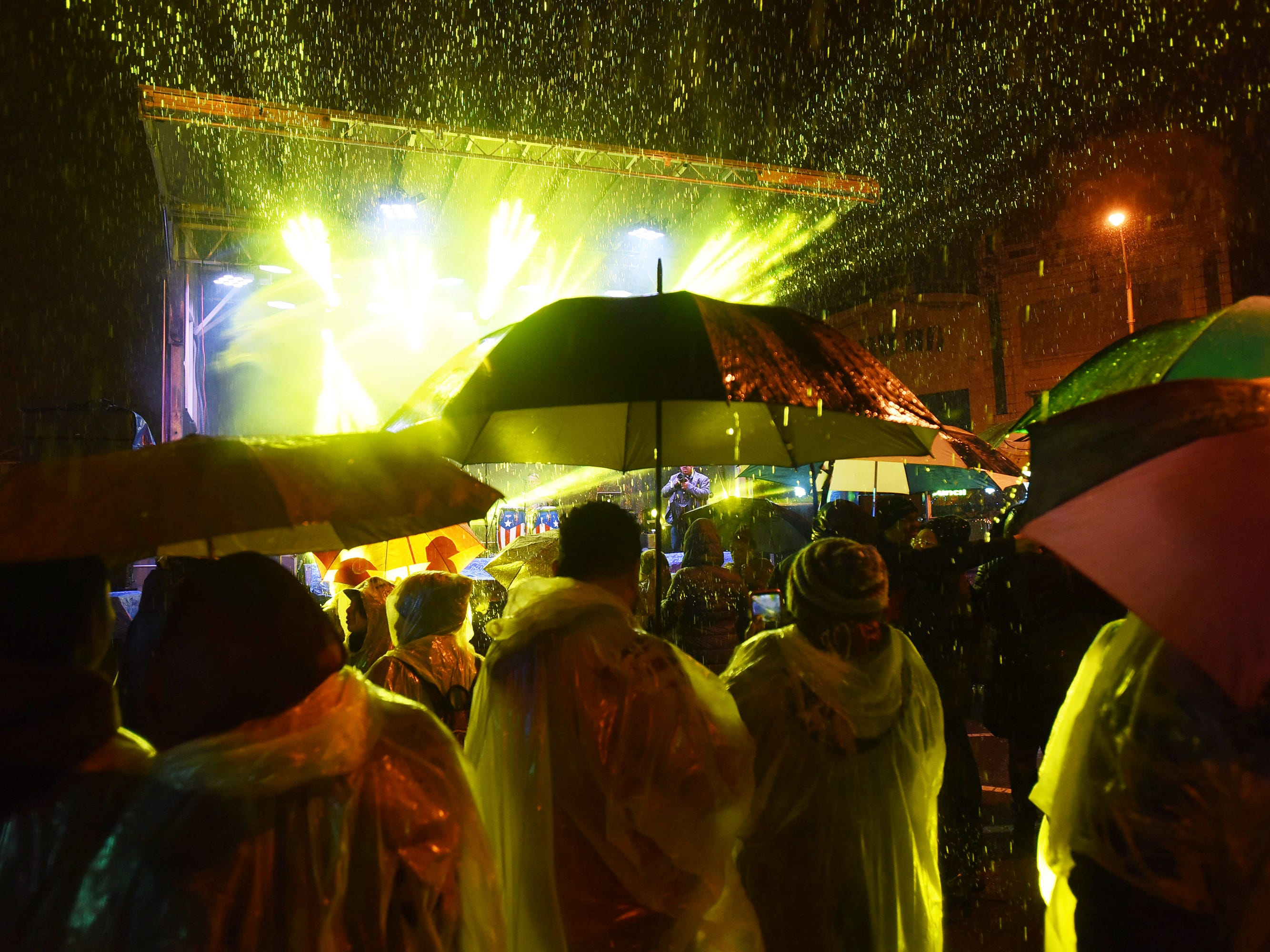 A crowd is seen in the rain as artists perform on stage as beams of light shoot into the sky   before the Pinata drops from the city's tallest building located at 663 Main Avenue at midnight in Passaic on 12/3118.