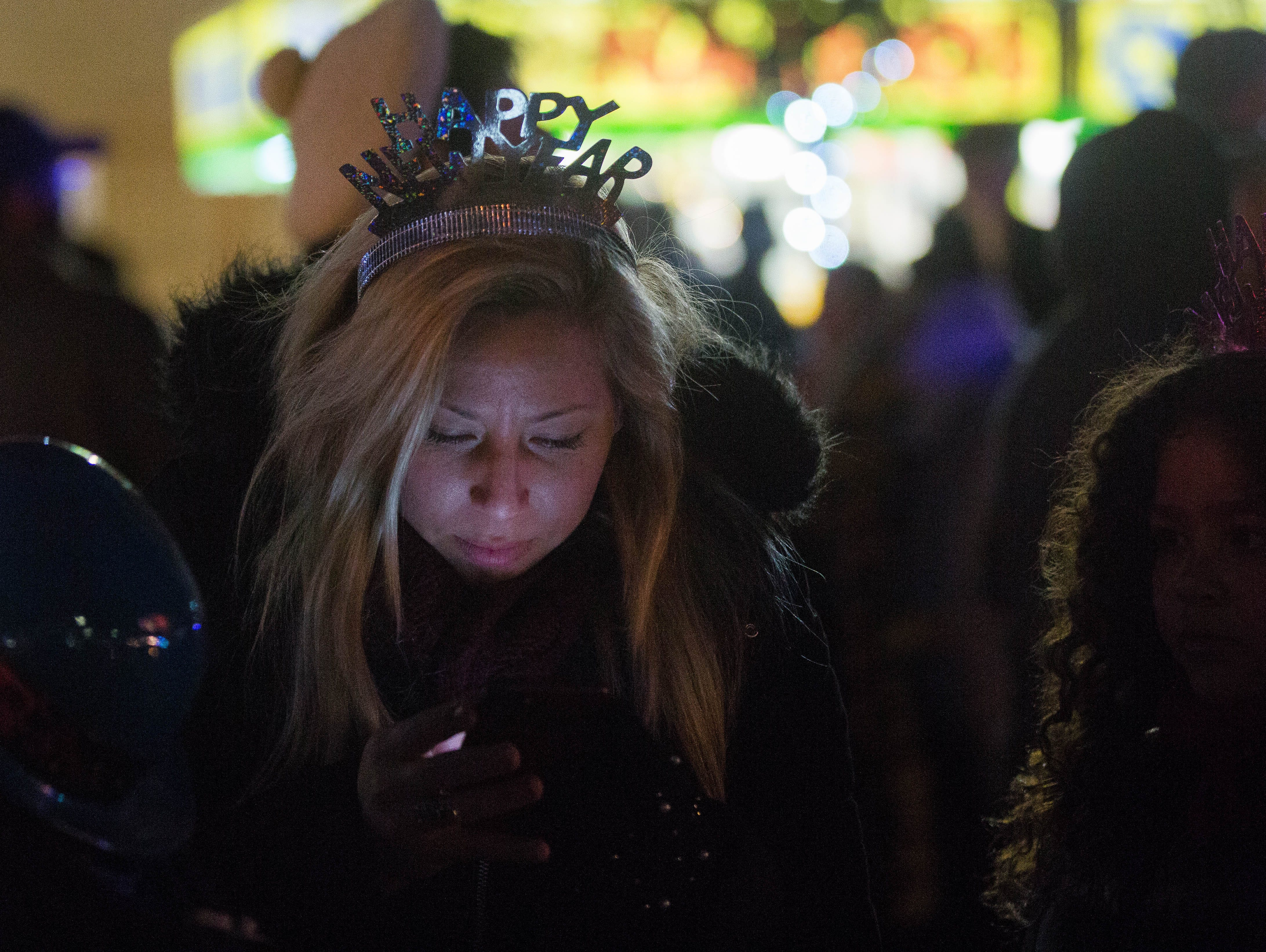 "Shannon Baltazar, looks at her phone as she wears a ""Happy New Year"" tiara, during the fifth annual Chile Drop Celebration, Monday December 31, 2018."