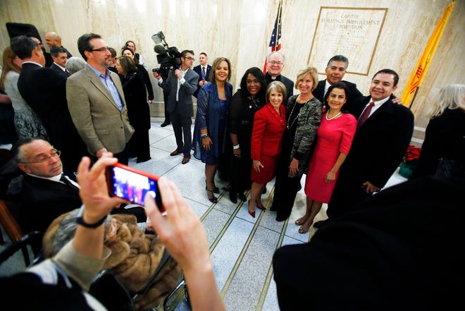 New Mexico Gov. Michelle Lujan Grisham poses for a picture with supporters Tuesday, Jan. 1, 2019, at the Capitol during a private swearing in ceremony in Santa Fe, N.M.  The reins of New Mexico state government are passing from one Latina governor to another as Democrat Michelle Lujan Grisham prepares for her inauguration at noon on New Year's Day.