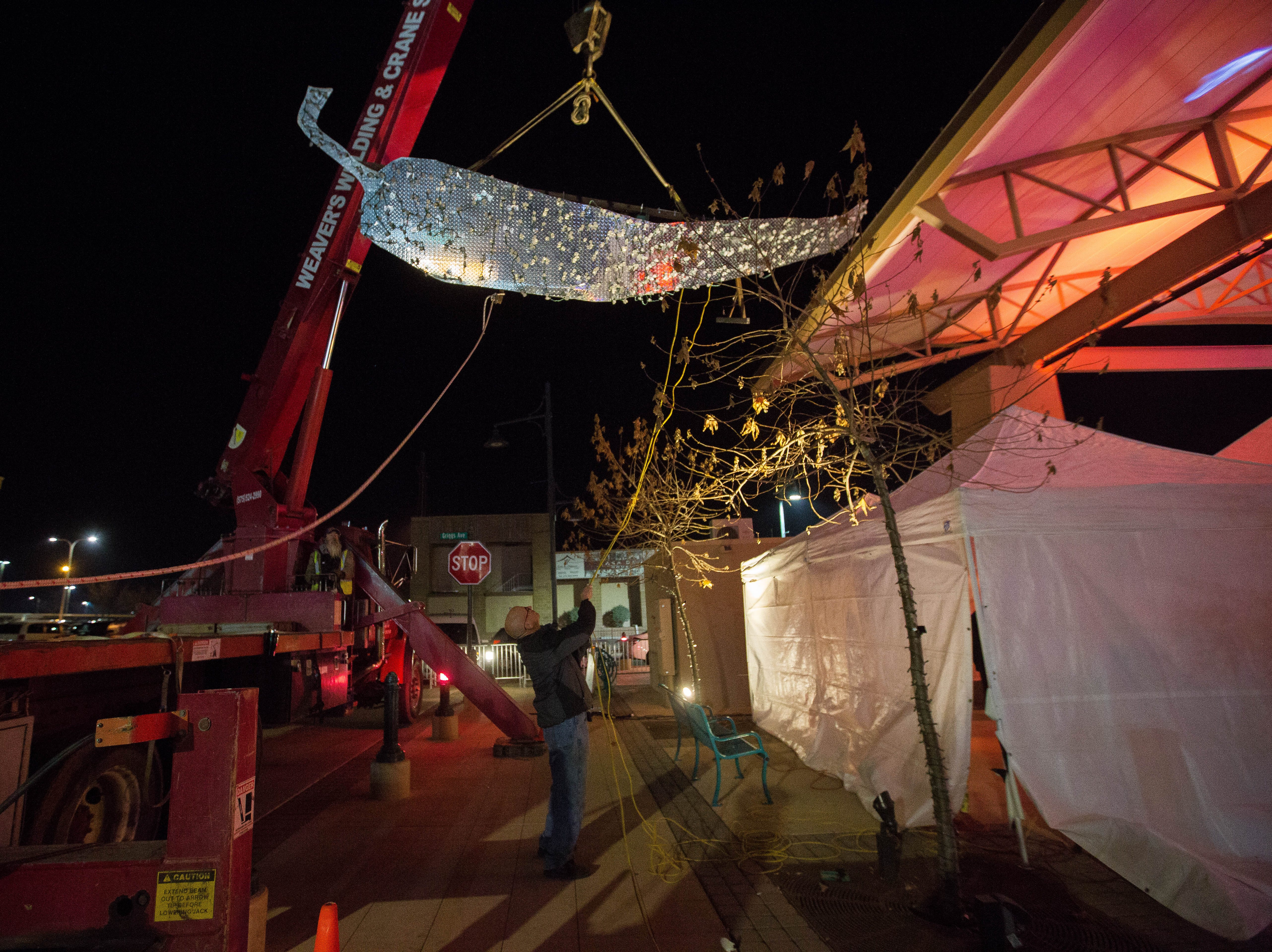 Russ Smith, one of the orginizers of the 2018 Chile Drop along with the Downtown Las Cruces Partnership, helps a crew with Weaver's Welding and Crane Services lift the chile into place, Monday, December 31, 2018 at the Plaza de Las Cruces.