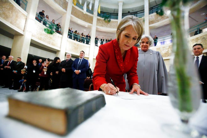 Michelle Lujan Grisham signs the oath of office to be the 32nd governor of the state of New Mexico, Tuesday, Jan. 1, 2019, at the Capitol during a private swearing in ceremony in Santa Fe, N.M., as her sister-in-law Sandra A. Grisham, a retired state District Court judge, watches.