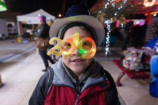 "Mauricio Alvarez, 8, wearing ""2019"" New Years glasses waits in line at the food trucks lining the Plaza de Las Cruces, Monday December 31, 2018 during the fifth annual Chile Drop celebration."