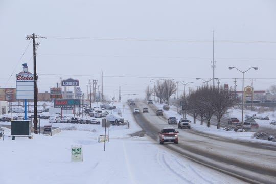 Bitter cold temperatures and snow on Tuesday did not hinder people from driving on East Main Street near Piñon Hills Boulevard in Farmington.