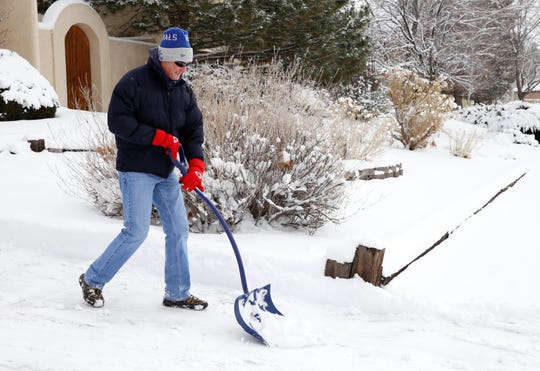 Dave Beavers shovels snow on Tuesday from his driveway on North Dustin Avenue in Farmington.