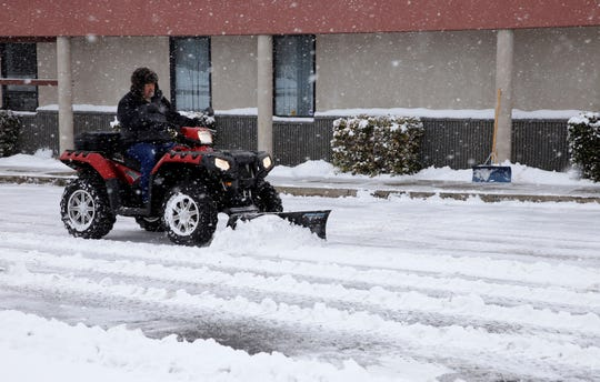Ray Schritter operates his four-wheeler to clear snow from the parking lot at Tax Pro on Farmington Avenue on Tuesday.
