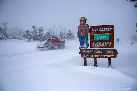 A snowplow struggles to keep up with snowfall near Angus Hill north of Ruidoso.